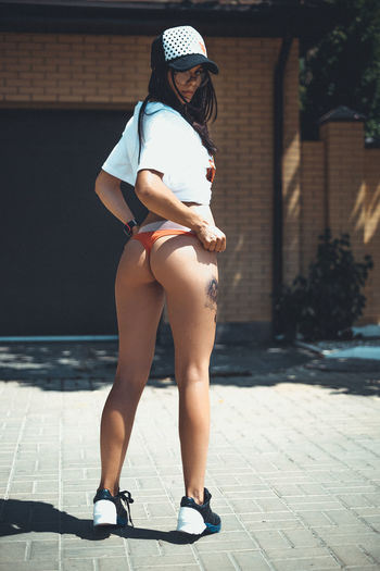Full Length Rear View Of Seductive Young Woman Standing On Road During Sunny Day