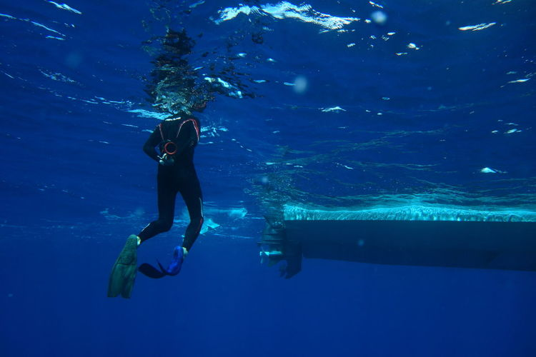 Low section of woman scuba diving undersea
