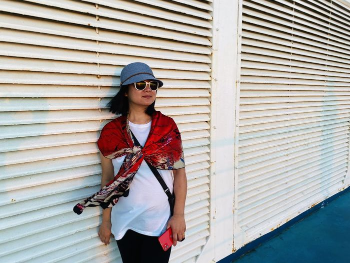 Woman wearing sunglasses looking away while standing against wall