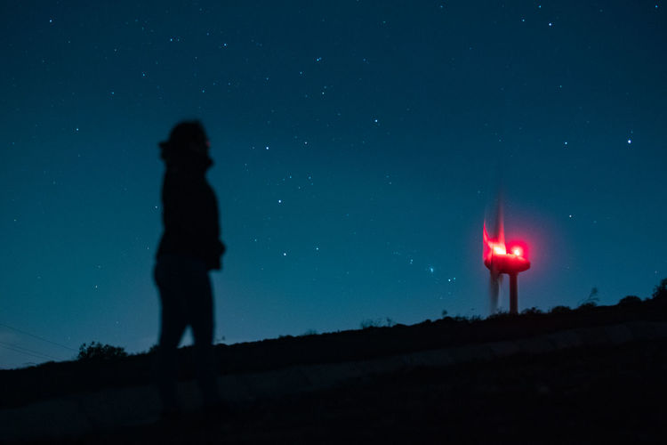 Silhouette person standing against sky at night