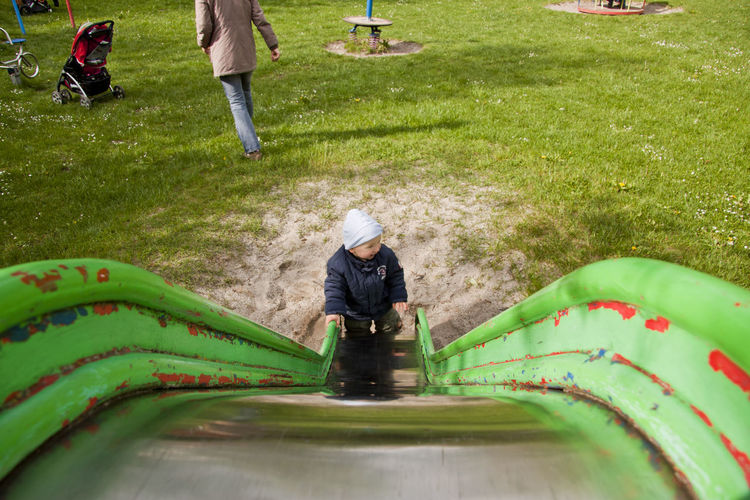 High angle view of baby boy standing by slide in playground
