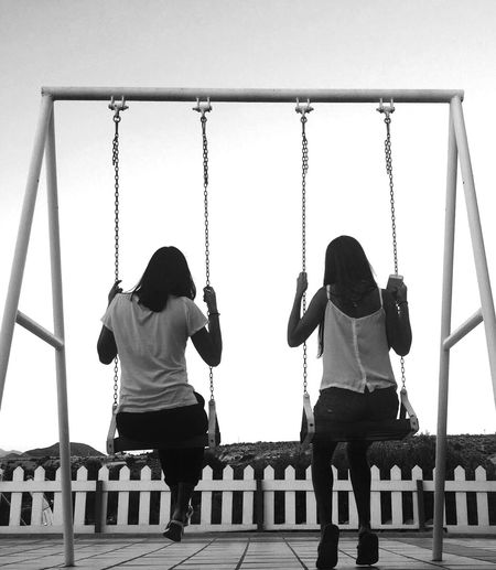 Rear view of women swinging against clear sky at playground