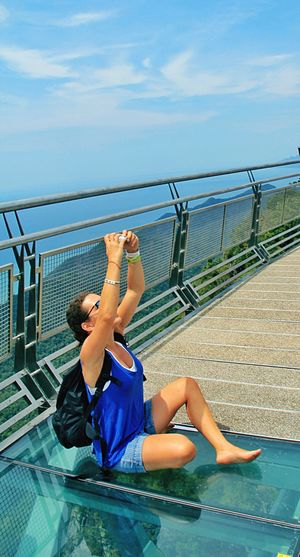 Woman Taking Selfie While Sitting At Observation Point Against Sky