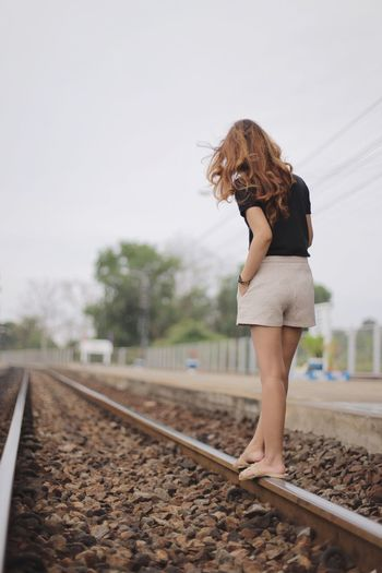 Woman walking on railroad track against sky