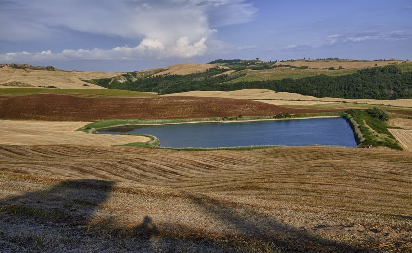 Scenic view of lake by hills at crete senesi against sky