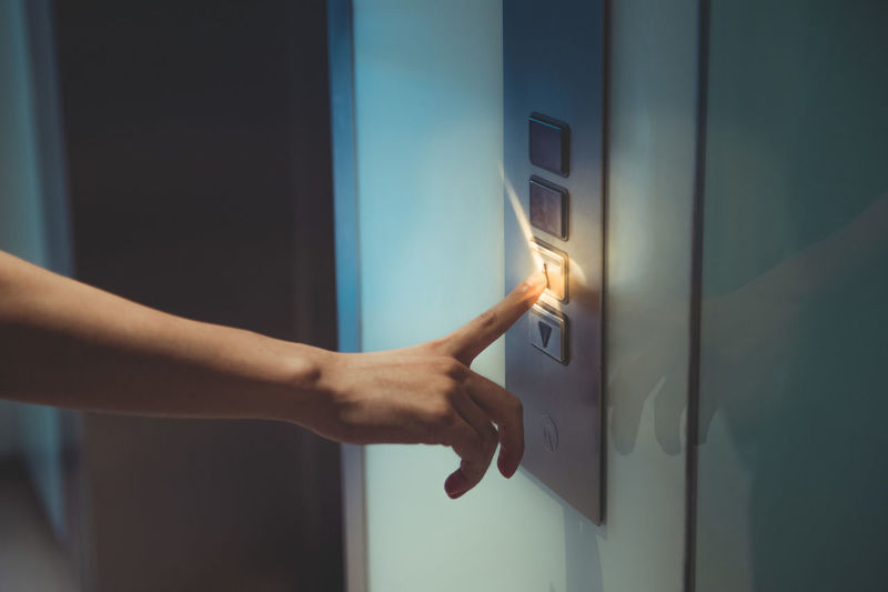 Human Hand Human Body Part Hand Real People One Person Body Part Indoors  Finger Touching Human Finger Control Technology Close-up Electricity  Illuminated Pushing Push Button Wall - Building Feature Door Human Limb