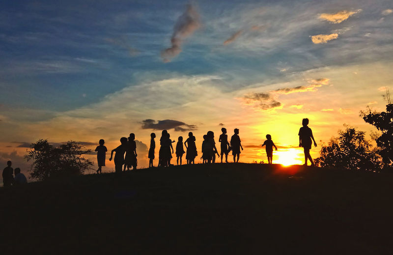 Silhouette kids standing against sky during sunset