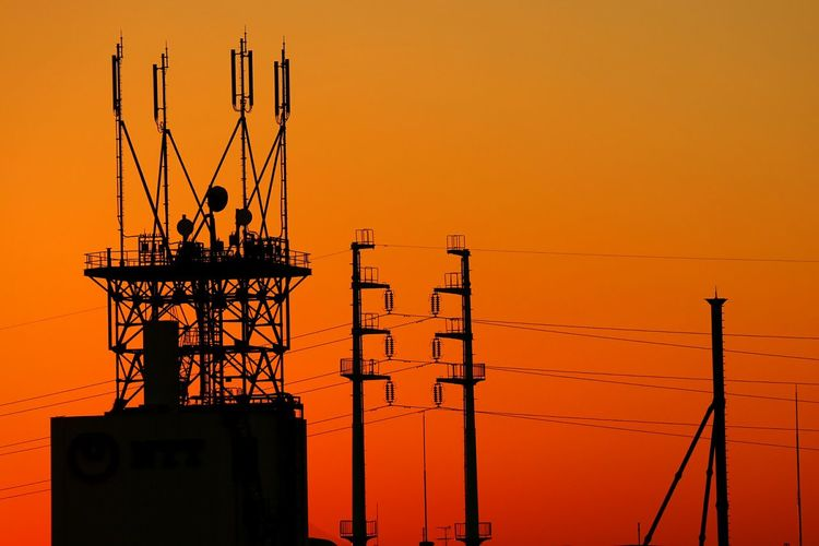 Silhouette electricity tower against orange sky during sunset