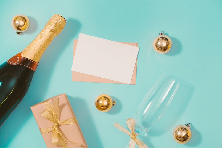 Flat lay Christmas or party background with gift boxs, champagne bottle, bows, decorations and wrapping paper in gold . Flat lay, top view Table Blue Indoors  High Angle View Paper Still Life Directly Above No People Colored Background Studio Shot Choice Close-up Kitchen Utensil Household Equipment Pen Variation Wood - Material Group Of Objects Metal Art And Craft Blue Background Blank Turquoise Colored