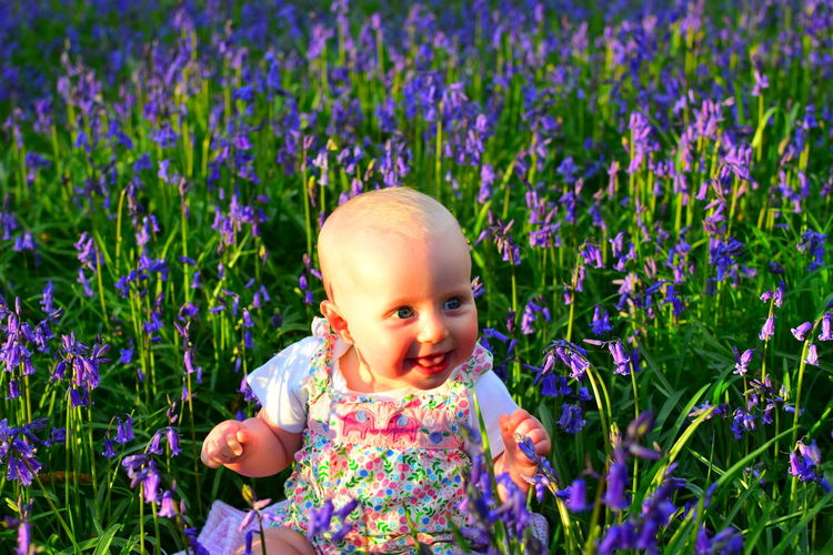 Portrait of cute girl with flowers on field