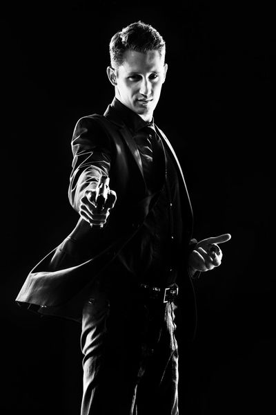 Franklin Miller's Sin City. Studio portrait in a low key with high contrast. Cosplay comic book characters. The man with the pistols. Shooter. Snapshot in motion Black & White Black Background Gun Low Key Sin City Standing Suit Black Black And White Black And White Collection  Black And White Photography Black And White Portrait Black Color Black&white Blackandwhite Blackandwhite Photography Comics Contrast Gunslinger  Handgun High Contrast Mooving One Person Portrait Three Quarter Length