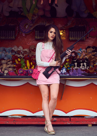 Portrait of young woman at amusement park shooting gallery
