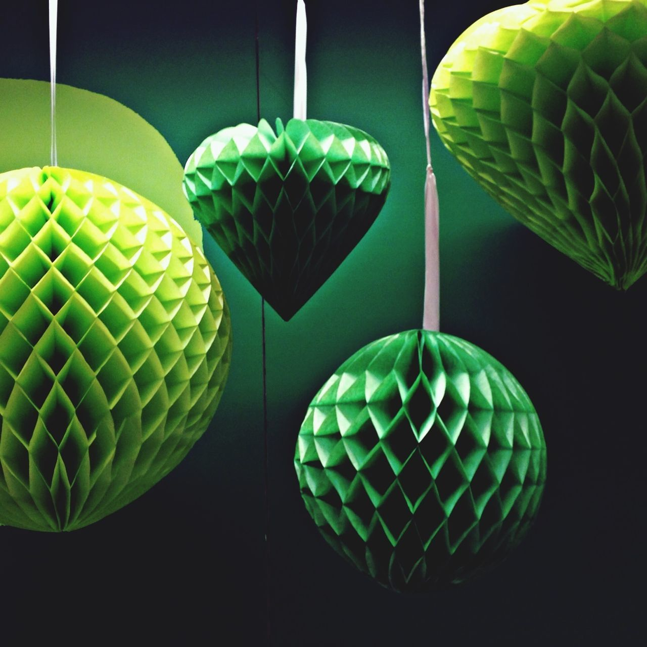 Close-up of green hanging lights against green background