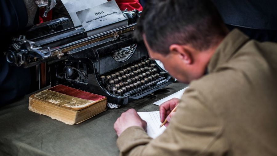 Side view of mature man writing while sitting at office