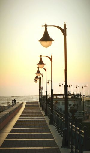 Street light by sea against sky during sunset