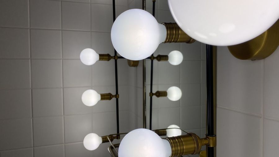 Low angle view of illuminated pendant lights hanging on ceiling at home