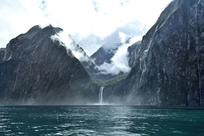 Scenic view of sea by mountains against cloudy sky at milford sound