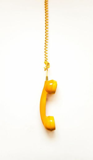 High angle view of yellow bell hanging on white background