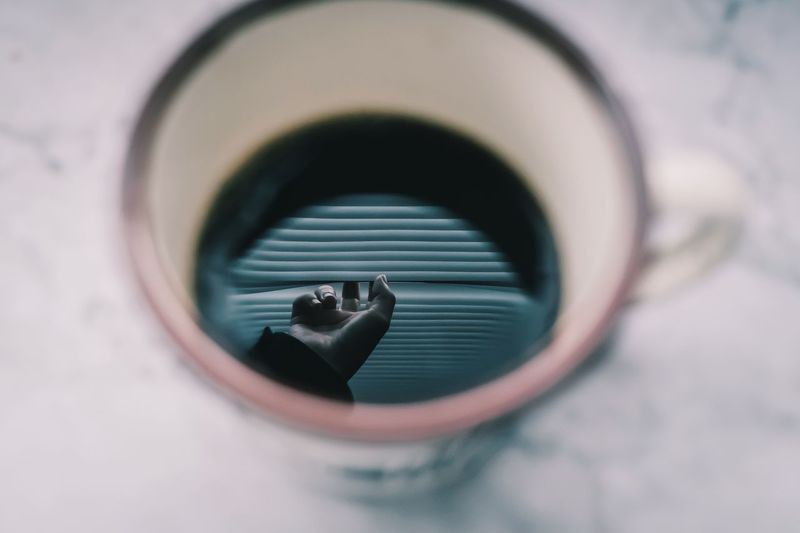 Cropped hand of person reflecting in coffee cup