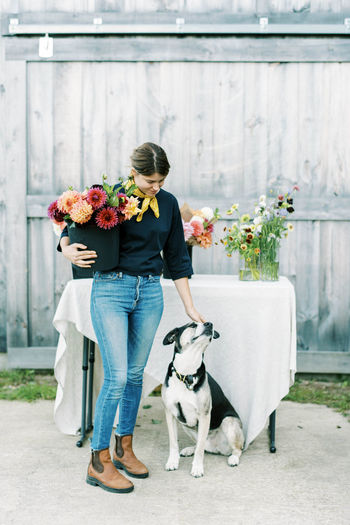 Woman with dog standing in flower pot