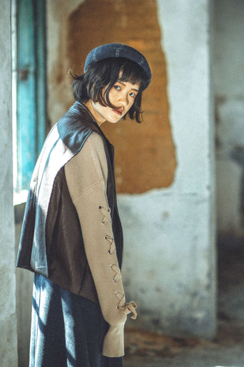 Portrait Of Young Woman Wearing Jacket While Standing In Abandoned Room