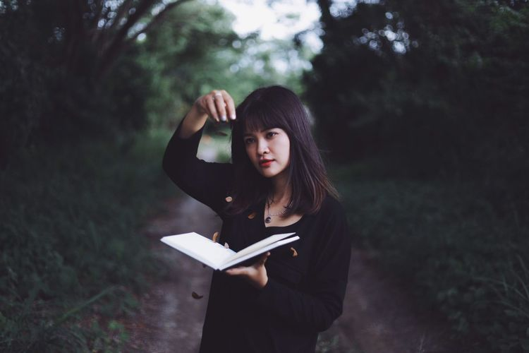 Young woman holding book while standing on tree