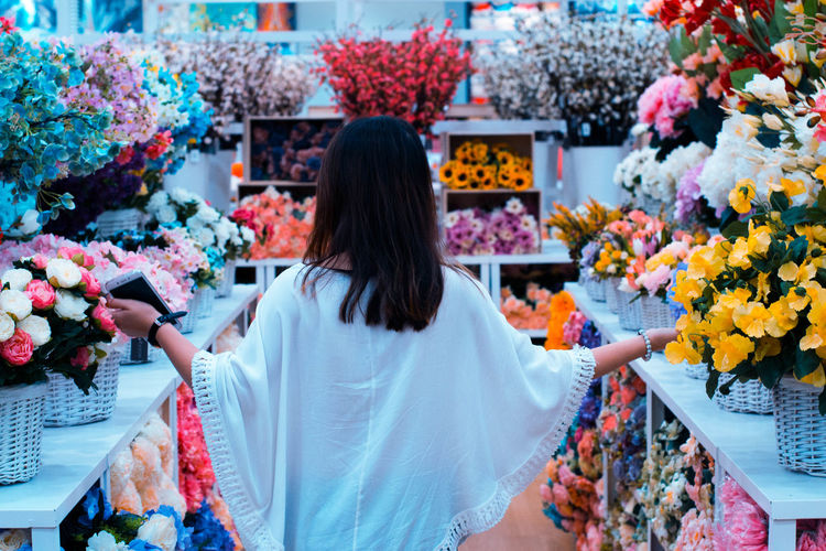 Rear view of woman amidst flowers in market