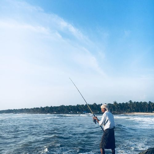Fisherman Fishing In Sea At Beach