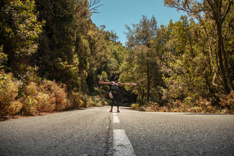 Rear view of person on road amidst trees during autumn