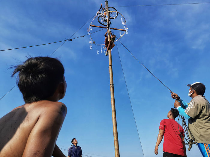 Low angle view of people on pole against sky