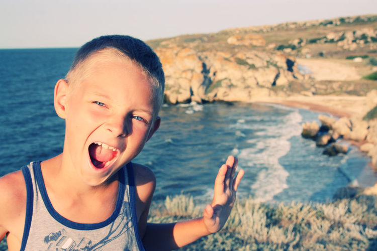 Portrait Of Boy Screaming While Standing Against Sea