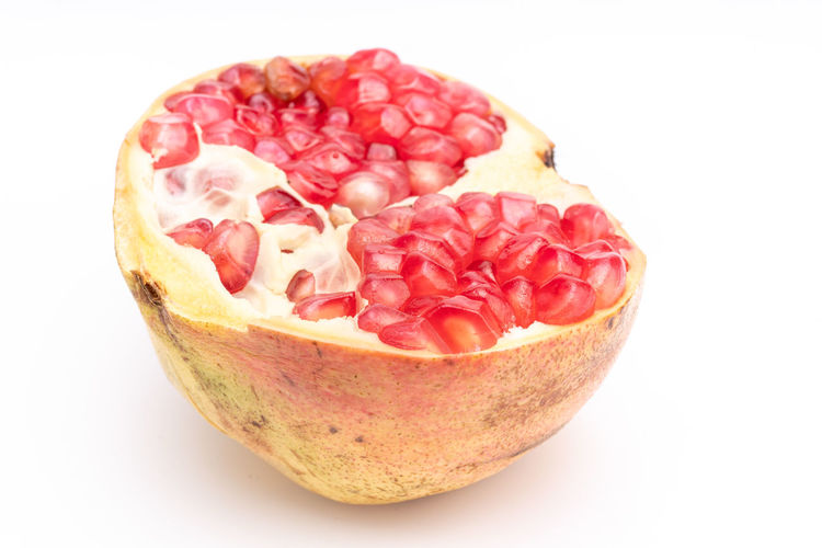 Attractive fruit in color, pomegranates Anticancer Barren Cold Temperature Delicious Drought Resistant Food Heart Insect Repellent Mature Adult Medicinal Micronutrients Nutrition Pomegranate Pomegranate Seeds Red Red Heart Rich Seeds Supplement Sweet Temperate Zone Tropical Vitamins Water Food And Drink Healthy Eating White Background Studio Shot Freshness Fruit Wellbeing Close-up Cut Out Indoors  Still Life No People Single Object Seed Cross Section Ripe High Angle View