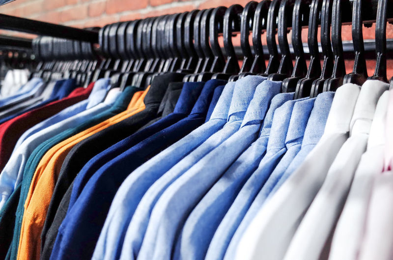 Large Group Of Objects Coathanger In A Row Clothing Rack Retail  Variation Multi Colored Choice No People Textile Indoors  Store Arrangement Hanging Clothing Store Shopping Collection For Sale Business Retail Display Fashion Order Sale Consumerism