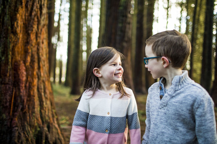 Siblings standing by tree in forest