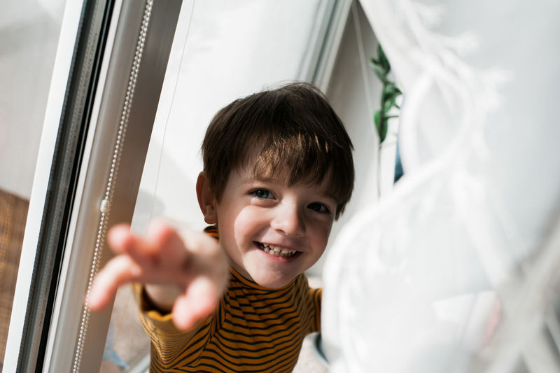 Portrait of smiling boy reaching while standing at home