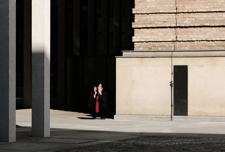 Side view of woman standing on footpath against building