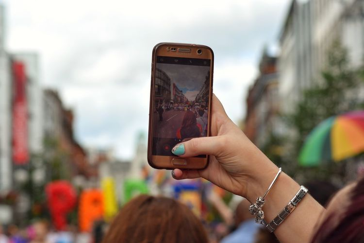 Close-up of woman photographing with mobile phone