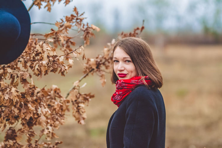 Portrait of smiling woman wearing warm clothing standing by dry plant