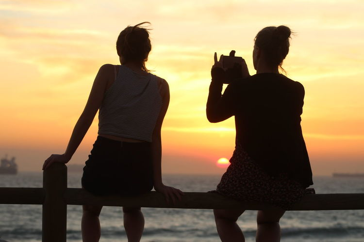 Rear view of woman photographing through smart phone while sitting with friend on railing during sunset