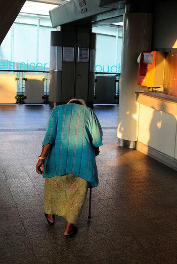 Rear view of senior woman walking at hallway