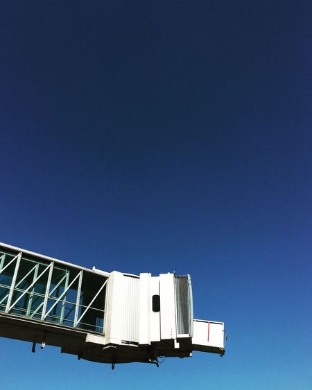 Low angle view of passenger boarding bridge against clear sky