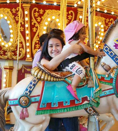 Carousel Child Childhood Girls Happiness Horse Merry Go Round Mother Daughter  Smiling Theme Park Amusement Park Bonding Carnival Outdoors