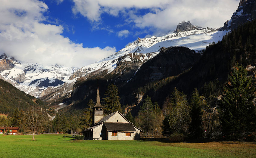 Church on field against snowy mountains