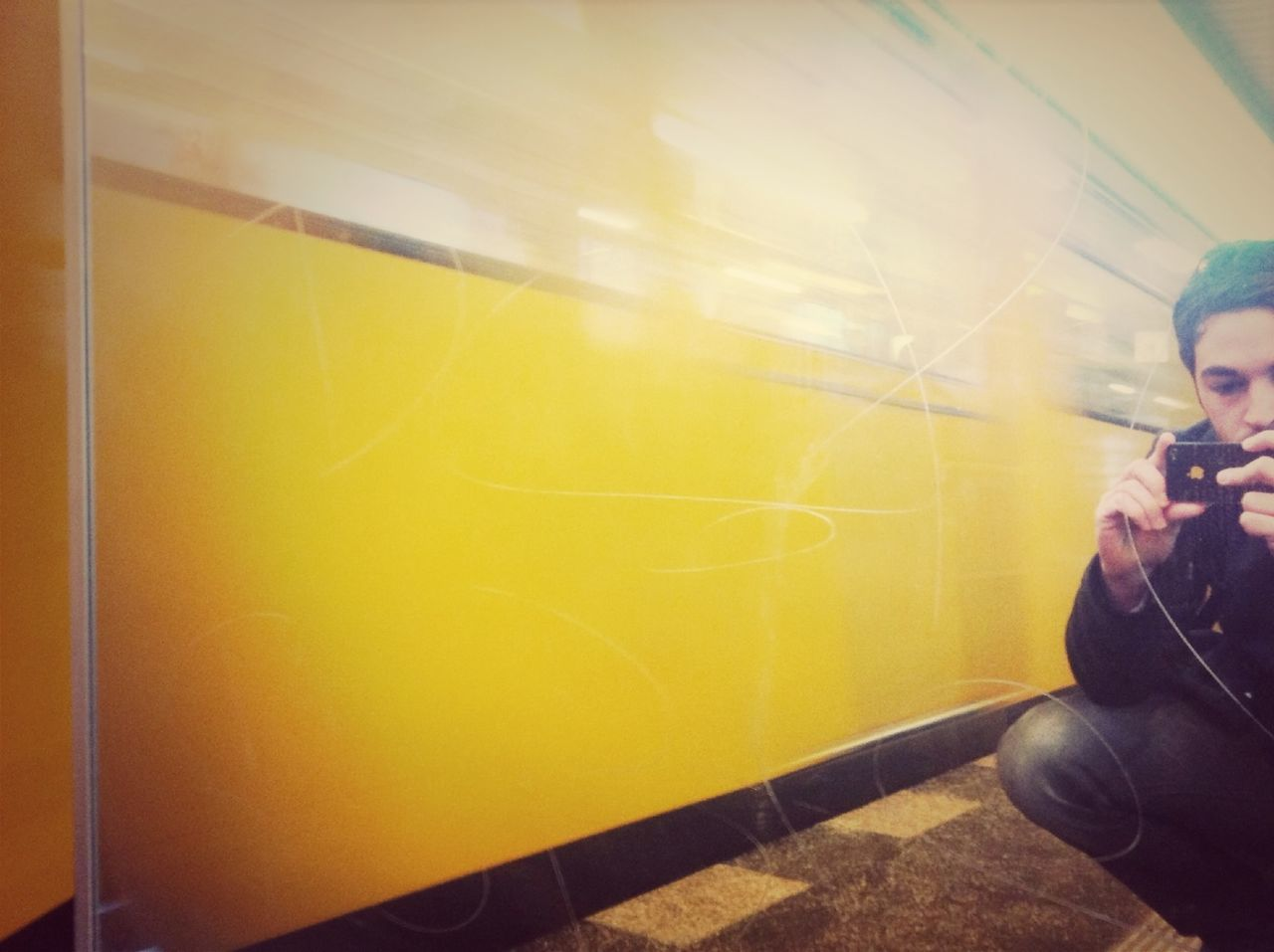 Cropped man photographing besides yellow wall