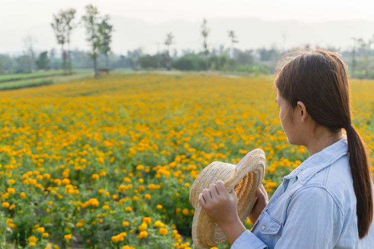 Marigold Portrait Flower Marigold Flower Farmer Selective Focus Lifestyles Outdoors Nature Plant Leisure Activity Care Check One Person Yellow Field Real People Land Landscape Growth Beauty In Nature Women Casual Clothing Agriculture Focus On Foreground Flowering Plant Hair Waist Up Hairstyle