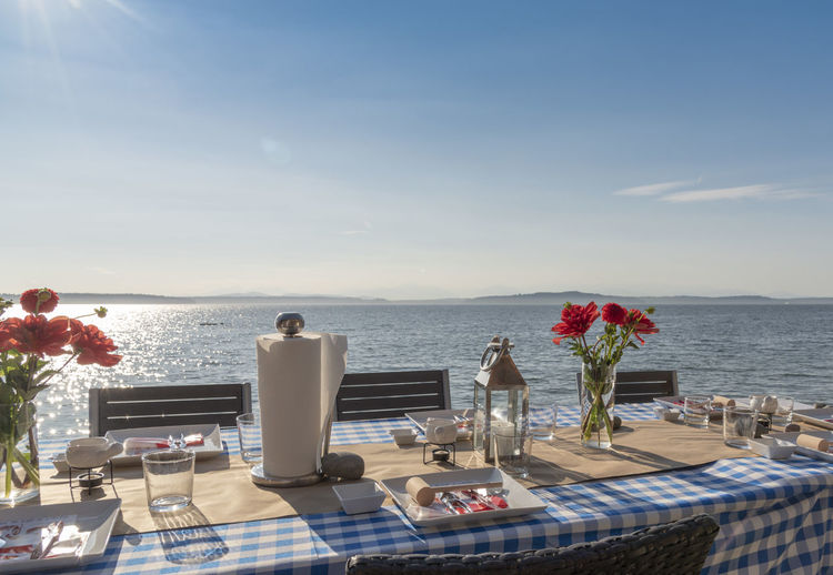 Arranged dining table at beach against blue sky during sunny day