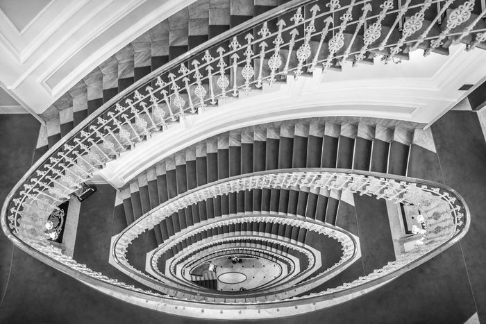 Monochrome image of spiral stairways made from marble with a red carpet and an elegant railing, view from above Above View Architectural Design Architectural Feature Architecture Built Structure Design Downstairs High Angle View Indoors  Marble Stairs No People Railing Red Carpet Stairs Spiral Spiral Staircase Spiral Stairs Staircase Stairs Steps Steps And Staircases