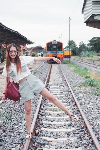 Portrait of woman on railroad tracks against sky