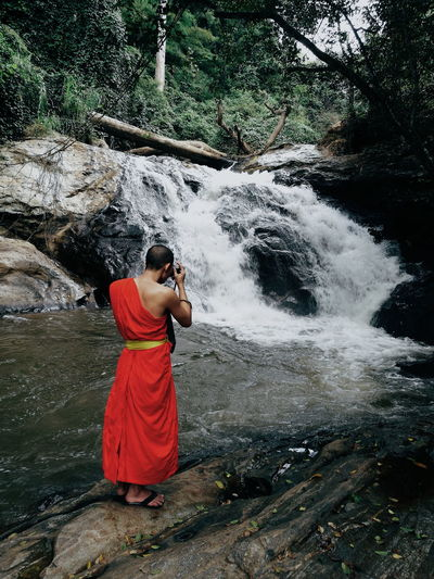 Monk photographing waterfall in forest