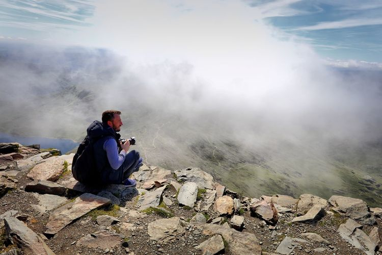 Side view of male hiker with camera sitting on mountain during foggy weather